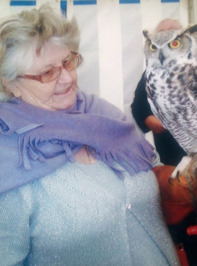 An elderly woman wearing a pale blue cardigan. She is holding a large black and white owl in her right hand.