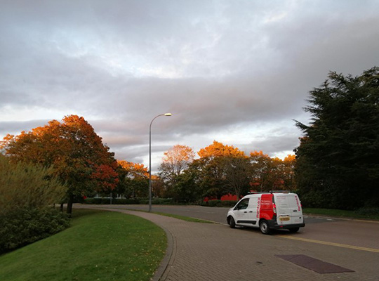 A landscape image taken from the side of the road on a grassy verge. The camera looks up to the sun setting over a cloudy sky. A white van is parked on the curb.
