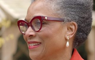 A close up image of a woman, Peaches Goulding, wearing red glasses. She is smiling, looking away from the camera.