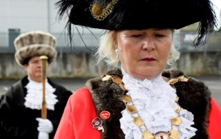 The Lord Mayor of Bristol wearing her ceremonial garments, looking down to the ground.
